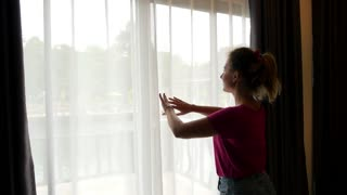 Beautiful Woman Arrives in Hotel Bedroom and Opens Drapes