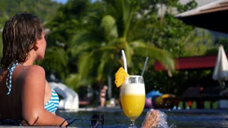 Beautiful Woman in a Pool with Fresh Healthy Pineapple Juice