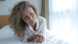 Beautiful Woman Lying on Bed and Smiling in Camera