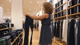 Beautiful Young Woman Choosing Jeans in Store