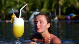 Beautiful Young Woman Drinking Cocktail in Swimming Pool