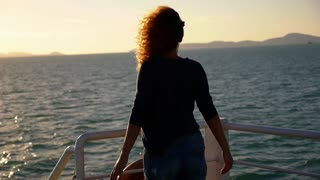 Beautiful Young Woman Standing on the Ship Deck and Spreading Arms towards Sunrise. Slow Motion.