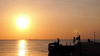 Boat on the Pier with Tourists at Sunset