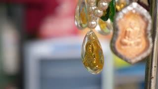 Buddha Amulet Hanging on Religious Necklace. Closeup