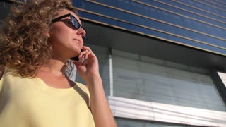 Candid Young Female Speaking by Phone in Business City