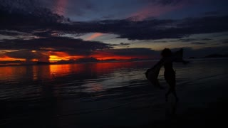 Carefree Woman Dancing in the Sunset on the Beach. Slow Motion.