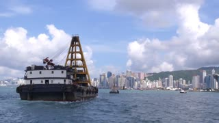 Cargo Ship in Victoria Harbor Against Hong Kong City