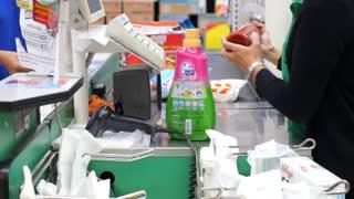 Cashier in Supermarket Serving Customers at Cash Desk
