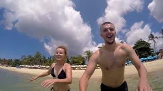 Cheerful Couple Swimming in Sea on Mattress