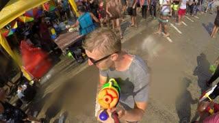 Cheerful Man Shooter with Water Gun at Street Celebrate Songkran. Slow Motion.
