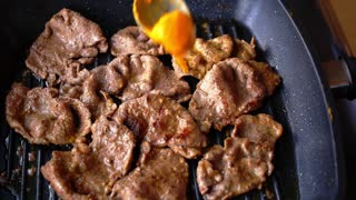 Cheese Sauce Being Added to Appetizing Roasted Slices of Beef on the Pan. Close up. Macro.