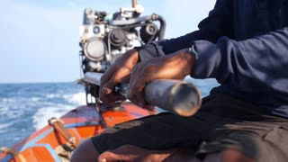 Close Up Hands of Fisherman on Long-tailed Boat, Motor Engine