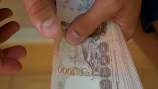 Close-up of a Man Hands Counting Banknotes. Thai Bahts.