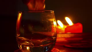 Close up of Pouring Alcohol Drink in a Glass against Burning Candles