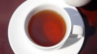 Close up of Pouring Milk into a Cup of Tea. Slow Motion.