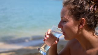 Close-up of Pretty Girl Drinking Water from Glass at Beach. Slow Motion.