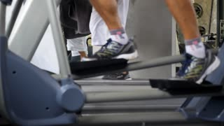 Close Up of Sport Men Legs Walking on Treadmills in Gym