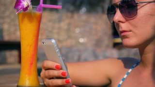 Close up of Woman in Vacations Texting in a Smart Phone