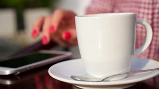 Close-up Of Woman Using Mobile Phone and Drinking Coffee
