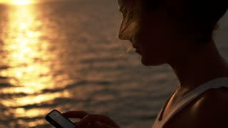 Close up on Young Woman Surfing Internet, Checking Social Networks on the Cell Phone against Amazing Seascape during Sunset. Slow Motion.