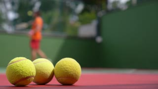 Close up View of Tennis Racket and Balls on Clay Tennis Court.