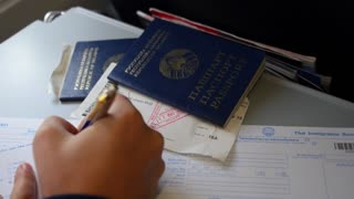 Closeup of Filling Immigration Card with Passports