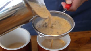 Closeup of Pouring Milk Tea in Cup in Cafe