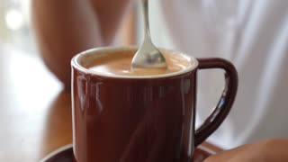 Closeup of Stirring Cup of Coffee with Foam and Milk in Cafe