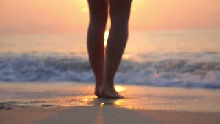 Closeup of Woman Bare Feet Walking at Beach at Sunset
