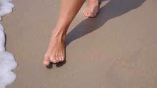 Closeup of Woman's Bare Feet Walking at Beach in Sea Foam