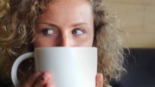 Closeup Woman with Beautiful Blue Eyes Drinking Coffee