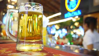 Cold Beer Glass on Bar or Pub Desk. Closeup.