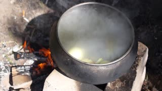 Cooking Fish Soup in Big Pot on Fire in Hike Trip in Camp