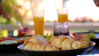 Couple Having Breakfast with Croissants, Jam, Fried Egg and Juice