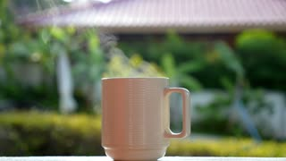 Cup of Hot Coffee with Steam Outdoors. Slow Motion.