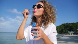 Curly Girl Blowing Bubble on the Beach