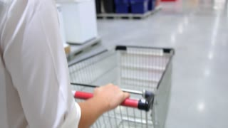 Customer Shopping with Trolley in Supermarket