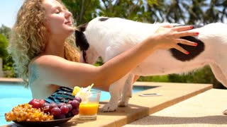 Cute Dog Kissing a Young Cheerful Woman at Summer Poolside.