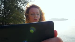 Cute Girl Taking Selfie by Tablet on a Sunny Day at Beach. Slow Motion.