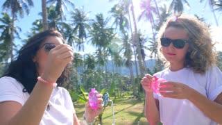 Cute Girls Blow Bubbles against Tropical Palm Trees