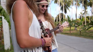 Cute Hippie Girls Playing Ukulele Guitar on Road and Hitchhiking