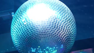 Disco Ball Reflecting Colorful Lights in Nightclub