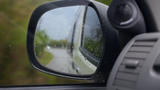 Driving in Rain. Side Mirror of Car.