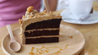 Eating Caramel Chocolate Cake with Fork in Cafe. Closeup.