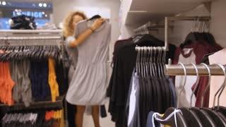 Fashion Girl Choosing Dress in Clothing Store