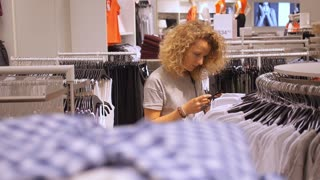 Female Buyer Choosing Clothes in Shopping Mall