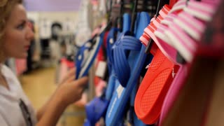 Female Choosing Flip-Flops in Sportswear Shoe Shop