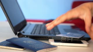 Female Hands Booking Tickets Using Notebook, Mobile Phone and Passport