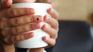 Female Hands Holding a Cup of Coffee. Closeup.