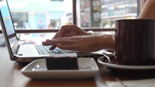 Female Hands Typing on Laptop Keyboard in Cafe